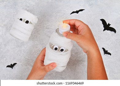 Handicraft from a jar. Mummy from a jar and bandages and bats on a light table. The concept for Halloween. DIY.