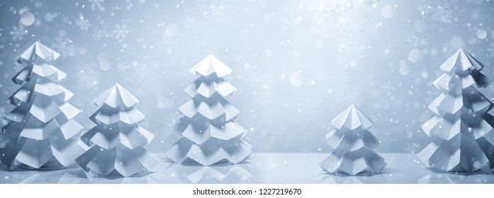 Handicrafted paper fir trees in snow