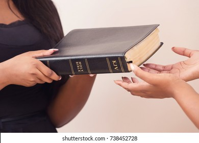 Handing A Bible To A Person Who Is Interested In Becoming A Christian