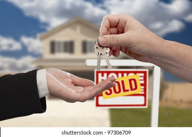 Handing Over the House Keys in Front of Real Estate Sign and Sold New Home.