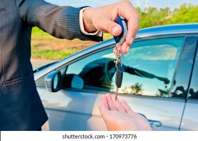 handing over keys of new car buyer