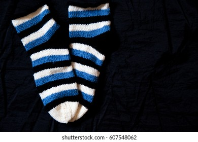 handknitted striped socks with black background