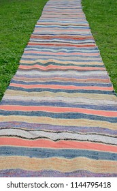 Hand-knotted stripy rug runner on the grassy ground