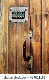 handle and access codes to the building on the wooden door.