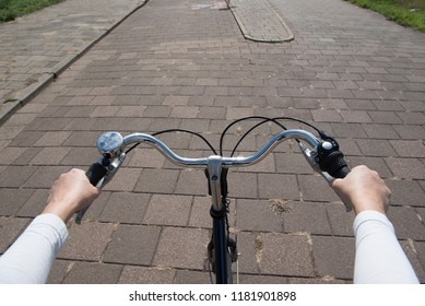 Handle bar on a bicycle seen from the point of view of the cyclist with street on the background and hands on the steering wheel