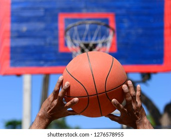 Handle basketball over ball hoop in basketball court outdoor.