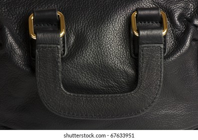 Handle of a black leather handbag