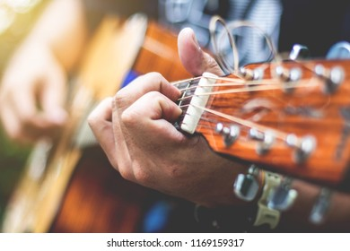 Handle Guitar Chords,Asian hipster man left hand catch chord and playing music.
