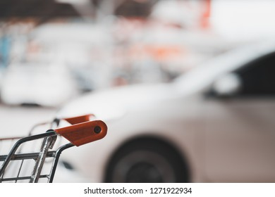 handle of shopping cart and blurred car at parking lot, autumn color tone