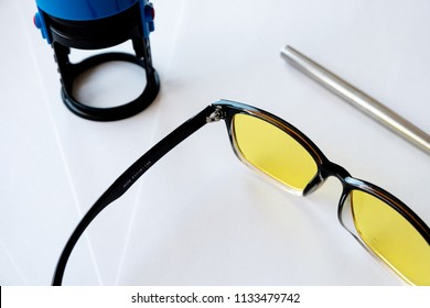 Handle with sunglasses are on a white background, next to a stamp on an imprint