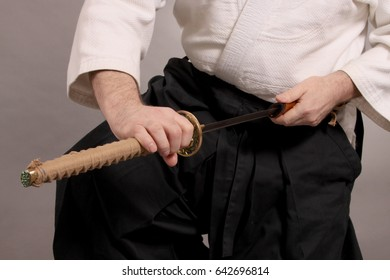 The handle of a sword of a katan is held by male hands against the background of the body dressed in a kimono.