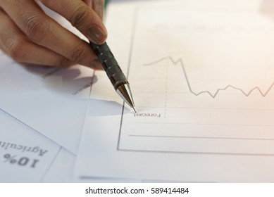 Handle using a pen with papers in forecast business concept