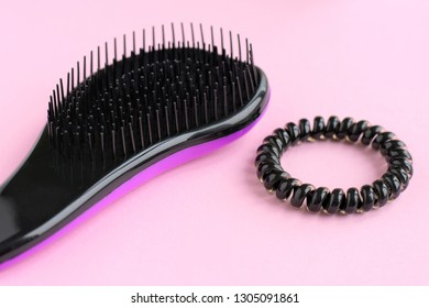 Handle violet plastic hair brush with black bristles with selective focus and spiral black scrunchies on neutral pink background. Hairbrush with elastic scrunchy for female hairstyle