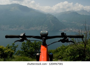handlebar and display of orange electric bicycle, e-bike, ebike, mountain, lake of Como, summer, sport, adventure, freedom, sun, alps, Lombardy, Italy