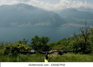 handlebar of electric bicycle, e-bike, ebike, background of high mountains, valley, lake of Como, summer, sport, adventure, freedom, sun, alps, Lombardy, Italy