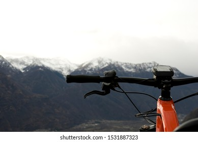 handlebar of an electric bicycle, e-bike, ebike, mountains covered by the first snow, autumn, sunset, Piedmont, Ossola Valley, Italy