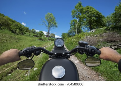 Handlebar of a motorcycle in the foreground in front of a mountain road