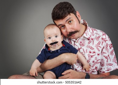 Handlebar Mustache family tradition-Funny portrait of Father and a son both with Handlebar mustaches, looking surprised towards the camera, horizontal, isolated on grey with vignette