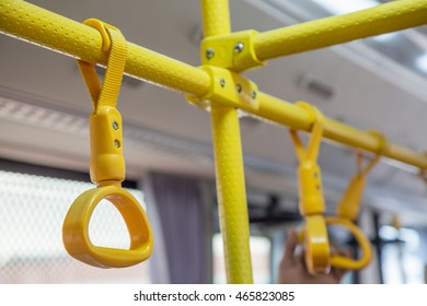 Handles on ceiling for standing passenger inside a bus in airport.