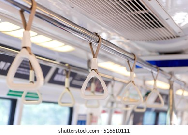 Handles on ceiling for standing passenger inside a bus.