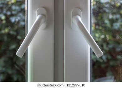 Handles on PVC structures are at an angle and the windows are not completely closed, with dusty glass through which you can see green bushes in the garden. Close-up.