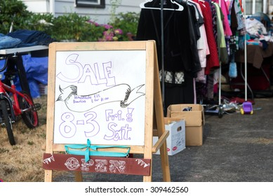 A hand-lettered sign advertises a home garage sale of used items.
