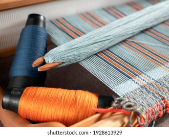 Handloom with shuttle on the blue warp threads and two bobbins with indigo and orange yarns. Vertical stripe weave