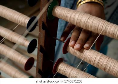 A Handloom Weaver preparing yarns  in India.