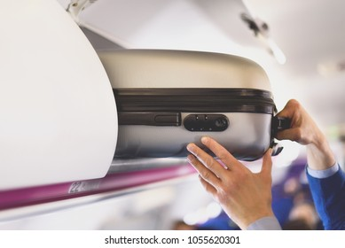 Hand-luggage compartment with suitcases in airplane. Hands take off hand luggage. Passenger put cabin bag cabin on the top shelf. Travel concept with copy space