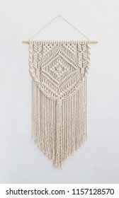 A handmade 100% cotton macrame wall decoration hanging on a white wall.