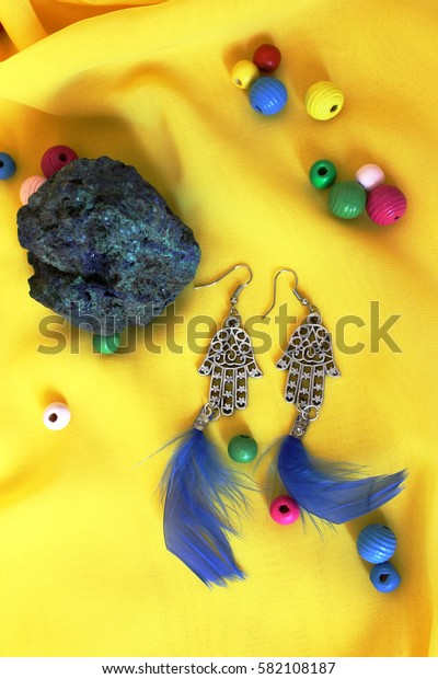 handmade accessories and blue stone on the yellow surface