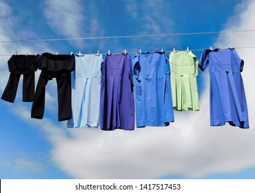 Handmade Amish dresses and black pants drying on a clothing line in the breeze, with blue skies and clouds in the background