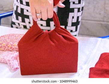 Handmade bag of folded red cloth. Furoshiki - Japanese art of folding fabric. Concept of fashion & reusable eco-bag contrary to plastic bags. Selective focus