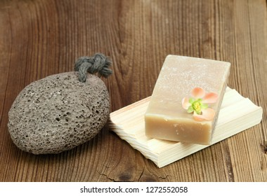 Handmade bar of soap and pumice stone.  Nettle and olive soap and pumice stone decorated with fresh flower  on wooden board.