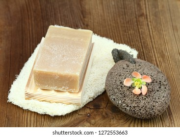 Handmade bar of soap, pumice stone and washcloth. Nettle and olive soap, facecloth and pumice stone decorated with fresh flower  on wooden board.