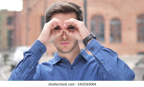 Handmade Binocular Gesture by Handsome Young Man Searching New Chance