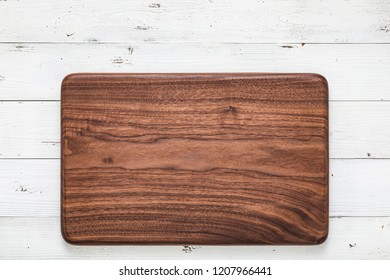 Handmade black walnut rectangular chopping board on a white wooden board top. Walnut texture background.