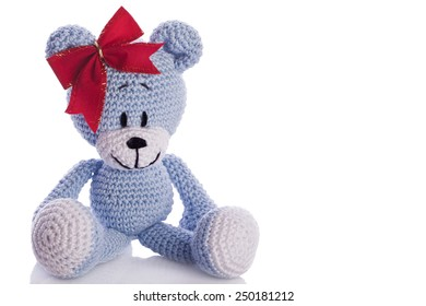 handmade blue teddy bear with red ribbon