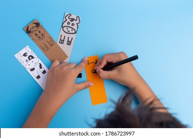 handmade bookmarks with bull or cow on blue background, paper craft for kids, hands draw, top view