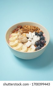 Handmade Bowl with healthy tasty breakfast of yogurt, smoothie with granola, nuts, bananas and berries on a blue table. Healthly food. Soft focus. A variety of ingredients and recipes.