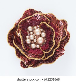 Handmade brooch of luneville embroidery hook in form of rose with pearls  isolated on white
