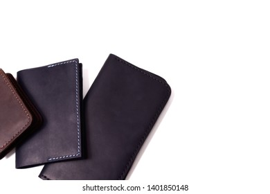 Handmade brown cardholder, black passport cover and purse isolated on white background closeup. Stock photo of isolated handmade luxury accessories.