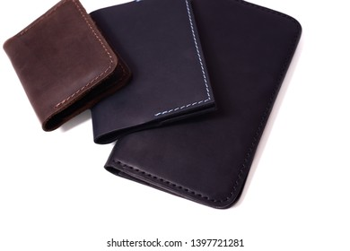 Handmade brown cardholder, blue passport cover and black purse isolated on white background closeup. Stock photo of isolated handmade luxury accessories.