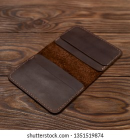 Handmade brown leather cardholder on wooden background. Cardholder have 4 pockets for cards. Stock photo with soft focus background.