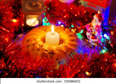 Handmade cake, Christmas decor, candles, Santa Claus toy.