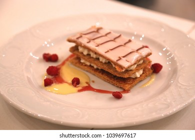 handmade cake, is watered with sweet sauce and two cake layers inside cream on a pink plate are strewed with wild strawberry,