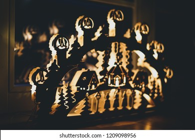 handmade candle arch from Germany based mountain range Erzgebirge standing on parquet and illuminates the floor on Christmas time