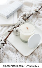 Hand-made candle with cotton branch on white cozy winter blanket