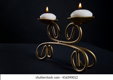 handmade candlestick for two candles, burning candles, on a black background
