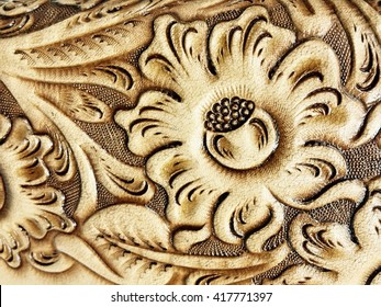 Handmade carving on leather, abstract art texture background.